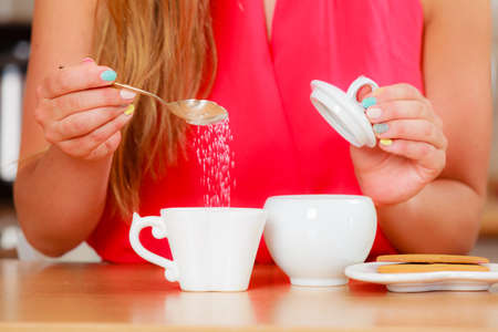 stimulate: Closeup of human adding sugar to tea or coffee at home. Person with hot beverage relaxing in kitchen. Stock Photo
