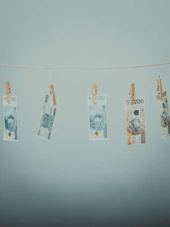 laundry line: Banknotes cash money hang on laundry line on gray grey background.