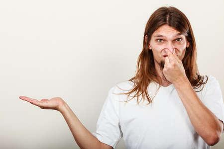 olfato: Expresión de muy mal olor. Joven de pelo largo sudorosa toma de la mano del hombre gesto de la mano empyt abierta para el producto. concepto de la sudoración.