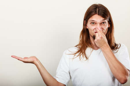 Expression of very bad smell. Young long haired sweaty man making hand gesture open empyt hand for product. Sweating concept.