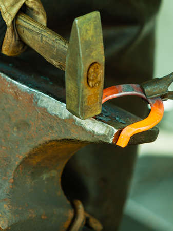 smithy: Making decorative element in the smithy on the anvil. Hammering glowing steel. Blacksmith forges a hot horseshoe.
