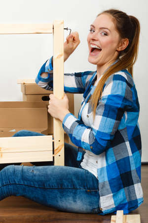Woman assembling wooden furniture using screwdriver. DIY enthusiast. Young girl doing home improvement.
