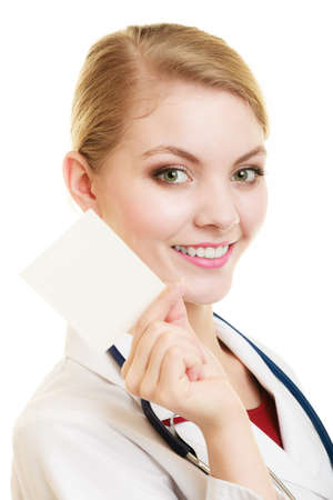 recommending: Woman in white lab coat recommending your product. Doctor or nurse with stethoscope holding blank copy space card isolated. Medical person for health insurance.