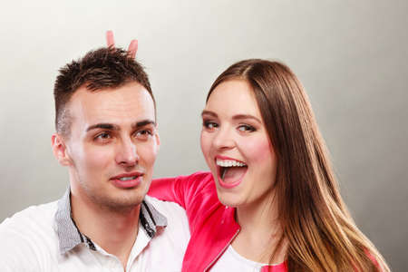 fooling: Happy couple having fun and fooling around. Joyful man and woman have nice time using fingers as bunny ears. Good relationship.