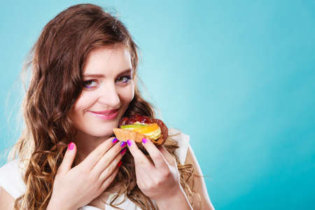 indulging: Sweet food sugar make us happy. Cute young woman colorful makeup nails holds fruit cake in hand blue background