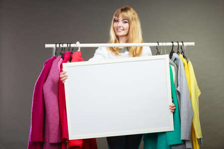 happy customer: Happy smiling pretty woman in wardrobe holding blank empty banner. Gorgeous girl customer in mall shop with copyspace. Fashion clothing sale advertisement concept. Stock Photo