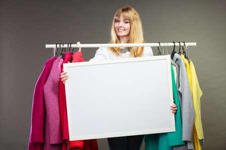 persona alegre: Sonriente mujer bonita feliz en el armario que sostiene la bandera en blanco vac�a. Al cliente Muchacha magn�fica en la tienda de centro comercial con copyspace. Ropa de moda anuncio de venta concepto.