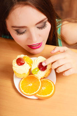 gluttony: Woman hidden behind table sneaking eating and tasting delicious cake with sweet cream and fruits on top. Appetite and gluttony concept.
