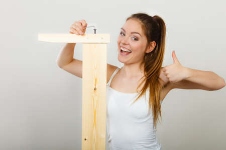 hex key: Successful soman assembling wooden furniture using hex key. DIY enthusiast. Young girl with thumb up doing home improvement.