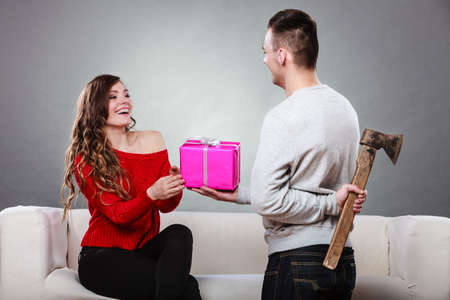 trusting: Sneaky insincere man holding axe giving gift present box to woman. Husband concealing hiding his true feelings from happy trusting wife. Untrue False intention. Relationship problems.