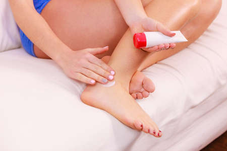 ointment: Woman fit girl putting ointment cream on bad injured ankle or applying moisturizer cosmetic cream on foot. Health skin care.