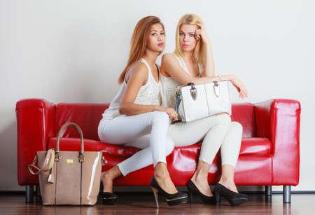 tacones rojos: traje elegante. moda femenina. carrera de dos mujeres rubias y se mezcla con ropa de moda zapatos de tacón alto con los bolsos que se sienta en el sofá rojo.