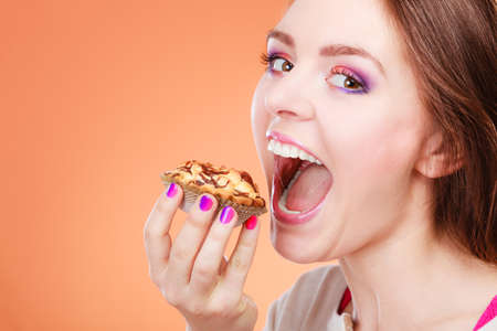 Bakery, sweet food and people concept. Woman wide open mouth holds cake cupcake in hand orange background Stock Photo