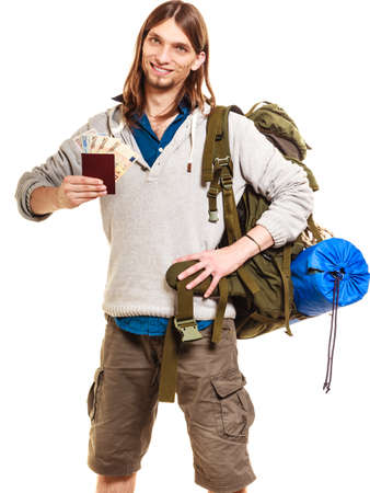 spendthrift: Man tourist backpacker holding passport full of money. Young guy hiker backpacking. Summer vacation travel. Isolated on white background. Stock Photo