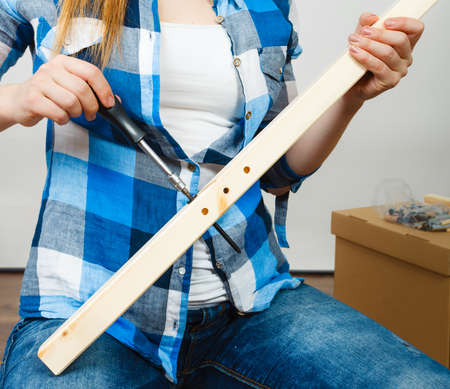 enthusiast: Human hands assembling wooden furniture using screwdriver. DIY enthusiast. Young girl doing home improvement.