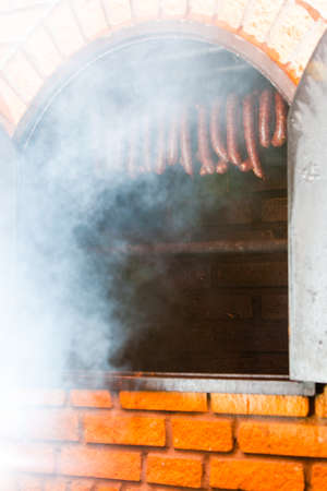 larder: Traditional food. Smoked sausages meat hanging in domestic smokehouse.