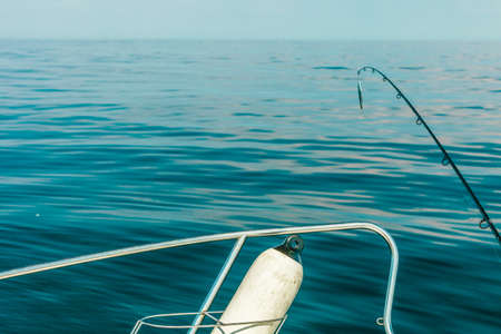 sportfishing: Sport and recreation. Fishing bait - rod with wobbler against the blue sea water surface Stock Photo