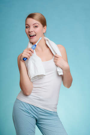 bad hygiene: Pretty young girl with electric brush cleaning white teeth using toothpaste. Happy woman clean her oral cavity caring about dental health.