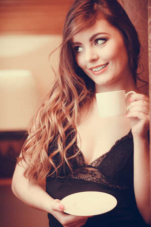 energizing: Sensual seductive woman in lingerie drinking cup of coffee by curtain at home. Young girl with hot energizing beverage stay awake. Caffeine energy.