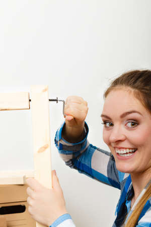 hex key: Woman assembling wooden furniture using hex key. DIY enthusiast. Young girl doing home improvement.
