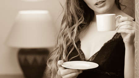 energizing: Closeup of sensual seductive woman in lingerie drinking cup of coffee by curtain at home. Girl with hot energizing beverage stay awake. Caffeine energy. Black and white.