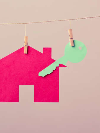laundry line: Red house with green key hang on laundry line on background. Selling and buying home concept. Stock Photo