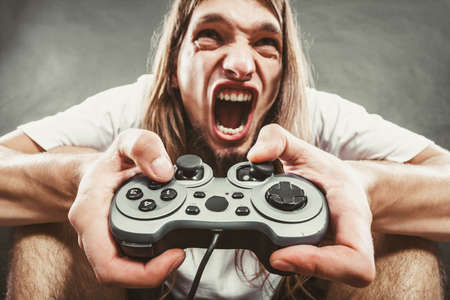 personas enojadas: Adicci�n. Hombre joven tensionado deprimida jugar juegos en el coj�n. Individuo enojado con la consola de juegos coj�n del regulador. Expresi�n facial.