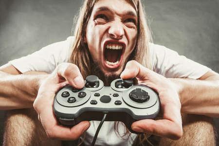 personne en colere: Dépendance. Souligné déprimé jeune homme jouant de jeux sur le pavé. Angry gars avec la console de jeu de pad contrôleur. Expression du visage.