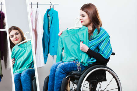 handicap people: Real people, disability and handicap concept. Teen girl handicapped woman sitting on wheelchair choosing clothes in wardrobe or  looking for some clothes in shop