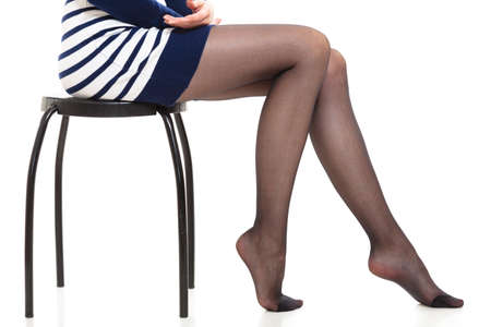 pantimedias: piernas de la mujer de belleza en medias negras. Parte del cuerpo de la muchacha atractiva delgada rayada que desgasta la falda del vestido y pantimedias aislados en blanco.