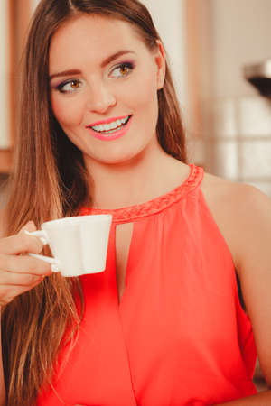 stimulating: Pretty woman drinking tea or coffee at home. Gorgeous young girl with hot beverage relaxing in kitchen.