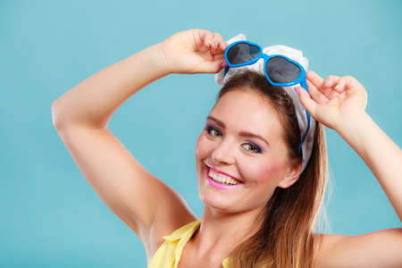 hairband: Portrait of happy smiling pretty pin up girl with hairband bow wearing heart shaped sunglasses. Attractive gorgeous young retro woman posing in studio on blue background.