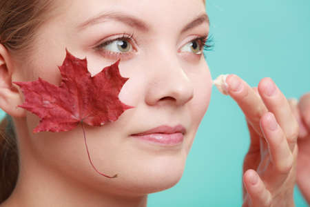 anti season: Skincare habits. Face of young woman with leaf as symbol of red capillary skin. Girl taking care of her dry complexion applying moisturizing cream. Beauty treatment. Stock Photo