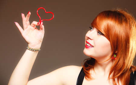 romantic heart: Happiness and love concept. Happy redhair woman smiling girl holding valentine red heart on gray. Valentines day.