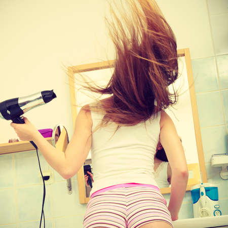 blow dry: Haircare. Beautiful long haired woman drying hair in bathroom back view