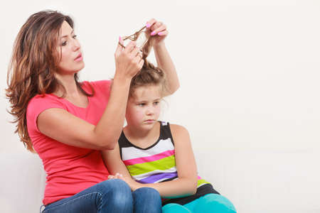 mothering: Mother combing daughter, care about hairstyle. Girl is unhappy mom pulling her hair. Important role in child life.