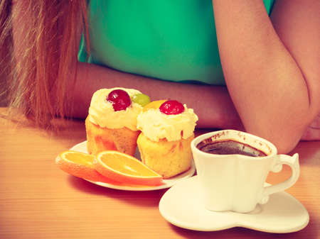 gluttony: Woman with cup of coffee and delicious gourmet sweet cream cake cupcake and orange. Lovely girl sitting in kitchen with hot beverage having breakfast. Appetite and gluttony concept. Stock Photo