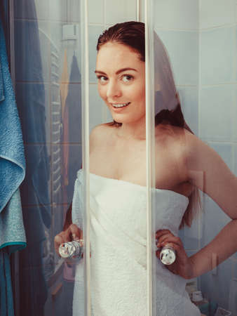 enclosure: Girl showering in shower cabin enclosure. Woman taking care of hygiene in bathroom. Stock Photo