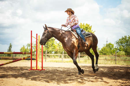 jumping fence: Activo caballo vaquera montar entrenamiento de la mujer occidental que salta sobre la cerca. competición deporte ecuestre y actividad. Foto de archivo