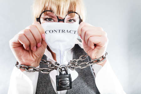 unusual angle: Business and stress concept. Terrified businesswoman in glasses with chained hands holding contract grunge background unusual angle view Stock Photo