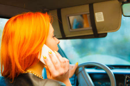 traffic: Concept of danger driving. Young woman driver redhaired girl talking on mobile phone smartphone while driving the car. Stock Photo