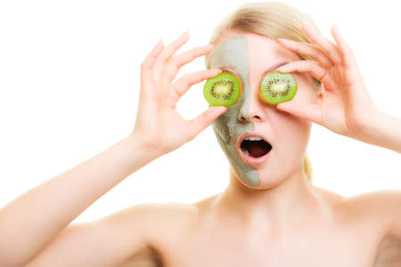 complexion: Skin care. Surprised woman in clay mud mask with kiwi fruit on face isolated. Girl taking care of dry complexion.