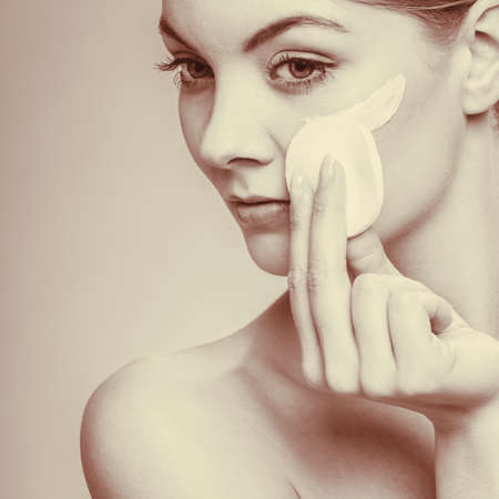 swab: Woman removing makeup with cotton swab pad from face. Young girl taking care of skin. Skincare concept. Sepia tone