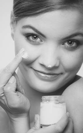 aging: Woman applying moisturizing cream on her face. Female taking care of her dry complexion. Keep your skin smooth concept. Black & white photo Stock Photo
