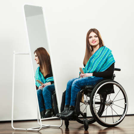 combing hair: Real people, disability and handicap concept. Teen girl handicapped woman sitting on wheelchair in front of mirror combing hair. Daily personal care