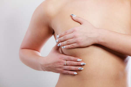 breast examination: Health care medical concept. Close up young woman examining her breasts for lumps or signs of breast cancer