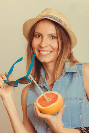 flirty: Happy glad woman tourist in straw hat holding sunglasses and grapefruit citrus fruit. Seductive and flirty girl. Healthy diet food. Summer vacation holidays concept. Stock Photo