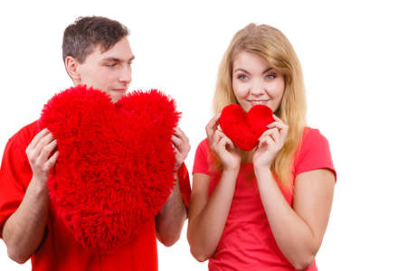 relationship love: Couple. Boyfriend and his girlfriend holding red heart shaped pillows love symbol. Romantic woman and man flirting. Valentines day happiness concept.