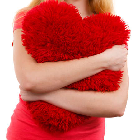 heartbreak issues: Woman blonde sad unhappy girl hugging red heart shaped big pillow studio shot on white. Heartbroken young female. Stock Photo
