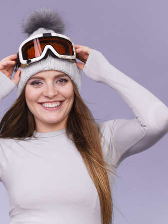 girl models: Attractive woman in winter cap gray sports thermal underwear for skiing training ski googles studio shot on blue.